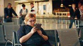 VARSOVIE, POLOGNE - AVRIL, 14, 2017 Jeune femme à l'aide de sa tablette sur le terminal d'aéroport vidéo 4K banque de vidéos