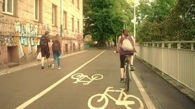 VARSOVIE, POLOGNE - 11 JUILLET 2017 Jeune femme avec le backsack montant sa bicyclette le long de route urbaine de vélo Photo libre de droits