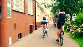 VARSOVIE, POLOGNE - 11 JUILLET 2017 Les jeunes faisant un cycle le long du trottoir de rue de ville banque de vidéos