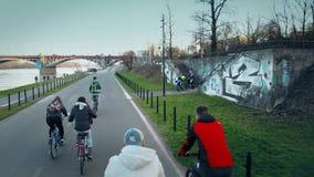 VARSOVIE, POLOGNE - MARS, 27, 2017 Tir aérien du groupe des jeunes montant leurs vélos le long de remblai de rivière de soirée Photos stock