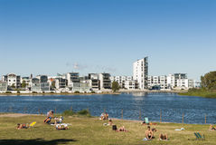 Varvsholmen Kalmar Sweden. People sunbathing opposite the modern residential area Varvsholmen (English: dockyard island) in Kalmar, Sweden stock photo