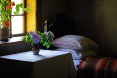 Vas av blommor i sovrummet av ett gammalt hus royaltyfri foto