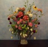 Vas av blommor mot den blåa väggen Arkivfoto