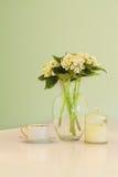 Vas av blommor och tekoppen i mjuka gröna pastellfärgade toner royaltyfria bilder
