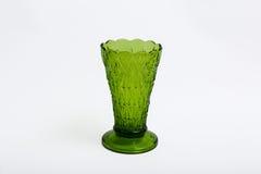 Vas för grönt exponeringsglas på en vit bakgrund Arkivbilder