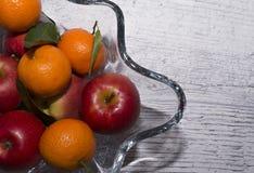 Vas med äpplen och mandariner Arkivfoton