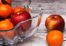 Vas med äpplen och mandariner Arkivfoto