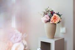 Vas med blommor som står på den lilla tabellen Royaltyfria Bilder