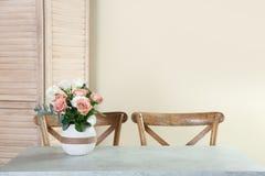 Vas med härliga blommor som beståndsdel av inredesignen på tabellen i rum royaltyfri fotografi