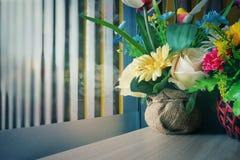 Vas med konstgjorda mångfärgade blommor bredvid fönstret Arkivbild