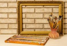 Vas med konstnärliga borstar, pastell och ramen på backgroen Royaltyfria Foton