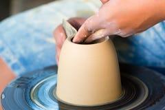 Vasaio che crea la ciotola dell'argilla sulla ruota di tornitura Immagine Stock