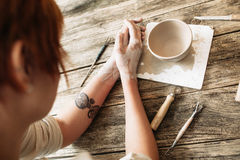 Vasaio femminile che esamina la ciotola dell'argilla, vista superiore fotografia stock libera da diritti