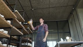 Vasaio maschio che guarda ai vasi fatti a mano durante il giorno del lavoro nelle terraglie archivi video