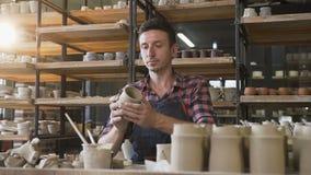 Vasaio maschio che guarda al cappuccio fatto a mano durante il giorno del lavoro nelle terraglie archivi video