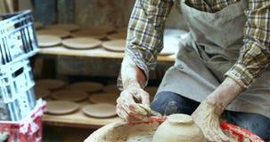 Vasaio maschio che rottama fuori l'argilla extra dalla ciotola ceramica 4k video d archivio