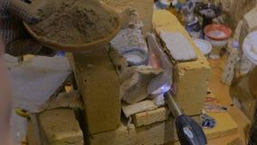 Vasaio maschio professionista che finisce tazza ceramica nello studio delle terraglie video d archivio