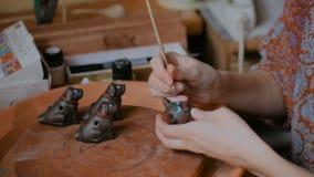 Vasaio professionista che dipinge il fischio ceramico del penny del ricordo nell'officina delle terraglie archivi video