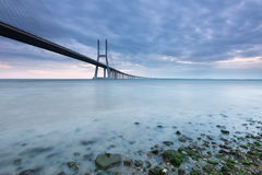 Vasco da Gama bridge in Lisbon at sunrise. One of the largest bridges in the world crosses the River Tagus. This amazing piece of engineering is a symbol of Royalty Free Stock Image