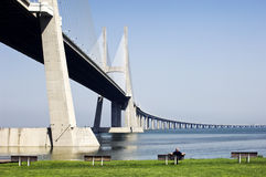Vasco da Gama Bridge/Portugal. A view of the Vasco da Gama bridge over the Tagus river in Lisbon, Portugal...a lone man sits on a bench enjoying the view Stock Photography