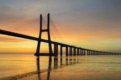Vasco da Gama bridge at sunrise, Lisbon. Vasco da Gama bridge in Lisbon, Portugal during sunrise with reflection in the Tagus river stock photo