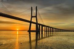 Vasco da Gama bridge at sunrise, Lisbon. Vasco da Gama bridge in Lisbon, Portugal during sunrise with reflection in the Tagus river royalty free stock images