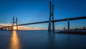 Vasco da Gama Bridge at Sunrise. Sunrise Long exposure of the Vasco da Gama Bridge in Lisbon and wooden pier, Portugal stock photography