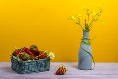 Vase με τα wildflowers Ένα καλάθι των φραουλών Μια φράουλα είναι στον πίνακα νεολαίες ενηλίκων Στοκ Φωτογραφία