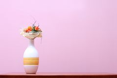 Vase against purple wall. Ceramic vase with dry flowers on wooden table against purple wall Royalty Free Stock Images