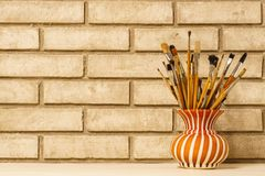 Vase with artistic brushes on the background of old white brick Stock Photos