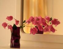 Vase avec des fleurs devant un miroir images stock