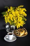 Vase avec la mimosa, la tasse de café et le strudel de clou de girofle sur un fond noir Photo libre de droits