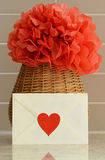 Vase basket with red tissue paper flower on kitchen counter top Stock Photos