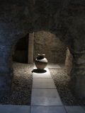 Vase - Baths of the Caliphate Alcazar. A large vase stands alone, lighted from above, as seen through an archway in the Baths of the Caliphate Alcazar located in Royalty Free Stock Photography