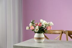 Vase with beautiful flowers as element of interior design on table. In room stock photo