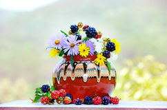 Vase with beautiful forest flowers and blackberries Stock Photo