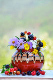 Vase with beautiful forest flowers and blackberries Stock Photos