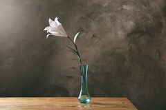 Vase with beautiful paper lily. On wooden table Stock Images