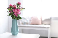 Vase with beautiful peony flowers on table. Indoors stock photo