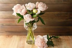 Vase with beautiful peony flowers. On table Stock Photography