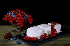 Ice cream with red currant berries. Vase with berries and cream ice cream on an old wooden table. Black background Stock Photos