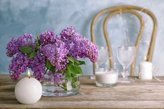 Vase with blossoming lilac on table indoors. Spring flowers Royalty Free Stock Images