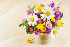 Vase with bouquet of flowers and healing herbs Stock Photo