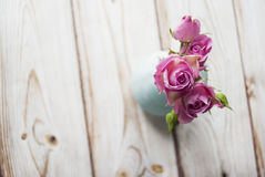 Vase with a bouquet of pink roses on a wooden background with the place for your text Stock Photos
