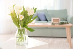 Vase with bouquet of tulips on table Stock Images