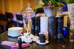 Vase with bread sticks. Glass vase with bread sticks on the table with plates, candles and pepperbox royalty free stock photography