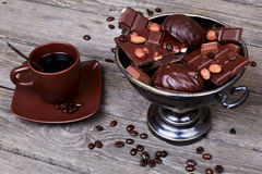 Vase with chocolate, nuts and coffee on a gray wooden background Stock Photography