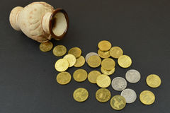 Vase with coins on table with black background Royalty Free Stock Image