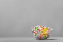 Vase with colour sweets. Colour fruit candy in a crystal vase on a gray background stock photos