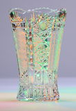 Vase of cut glass. Vase of amply cut glass in light green and amber light in front of neutral grey background Stock Photography
